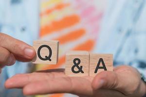 q och ett alfabet på träkub i handhåll med bakgrund foto