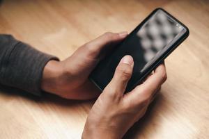 man använder smartphone på träbord, söker, surfar, socialt foto