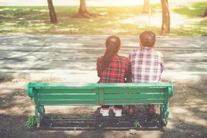 unga kärlekspar som sitter tillsammans på bänken. foto