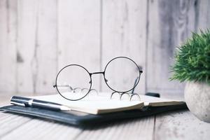 anteckningsblock, glasögon och en penna på träbord foto
