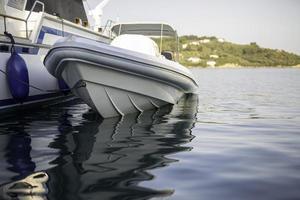 liten motorbåt vid kajen med vackra reflektioner i vattnet. foto