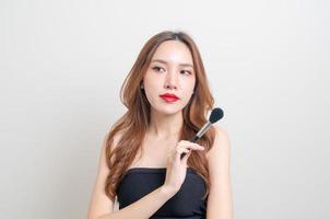 porträtt vacker asiatisk kvinna med sminkborste på vit bakgrund foto