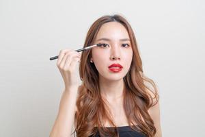 porträtt vacker asiatisk kvinna med sminkögonborste på vit bakgrund foto
