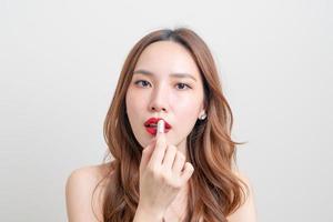 porträtt vacker asiatisk kvinna som gör upp och använder rött läppstift på vit bakgrund foto