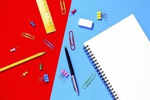 ovanifrån, anteckningsboken och pennan på en blå, röd bakgrund. foto