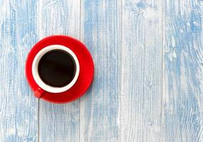 röd kopp kaffe på träbord blå bakgrund foto