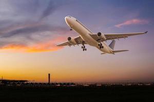 kommersiellt flygplan startar vid solnedgången foto