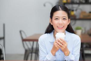 ung asiatisk kvinna som dricker kaffe och ler. foto