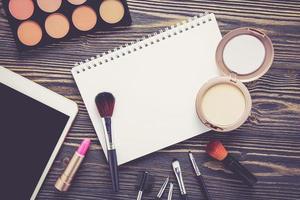 ovanifrån en samling kosmetisk smink och anteckningsbok på träbord. foto