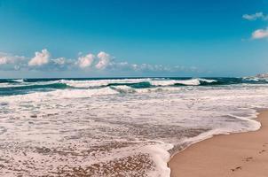 fotspår i sand på Indiska oceanens strand, turkosa vågor foto