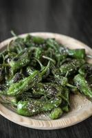 pimientos padron grillad spanska gröna chilipeppar tapas mellanmål på tallrik i rustik santiago de compostela restaurang foto
