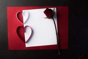 rött hjärtapapper och tomt med anteckningskort på röd bakgrund. foto