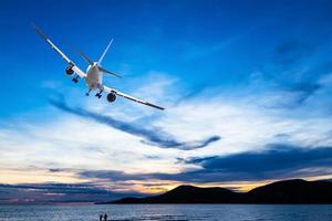 kommersiellt flygplan som flyger över havet vid solnedgången foto