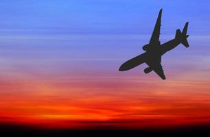 silhuett kommersiellt flygplan som flyger vid solnedgången foto
