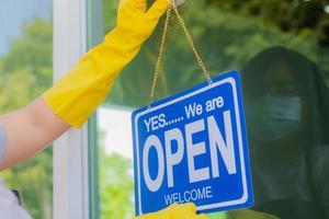 ägaren till butiken hänger en skylt för att öppna ett företag framför foto