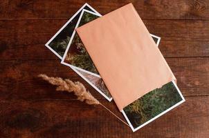 komposition med foto inbäddat i beige kuvert ligger på träbord
