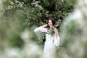 porträtt av ung kvinna i parken i de blommande grenarna foto