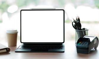 bärbar dator tom skärm med edc -maskin på ett bord i ett kafé foto