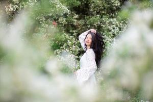 porträtt av en vacker ung kvinna i parken i blommande grenar foto