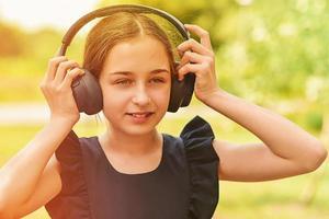 glad liten flicka som bär hörlurar. foto