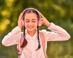 utomhus tonårsflicka som lyssnar på musik med trådlösa hörlurar foto