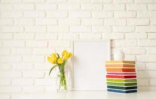 gula tulpaner i en glasvas och tom fotoram foto
