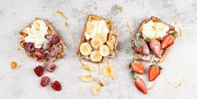 våfflor med frukt och bär, grädde och honung i en tallrik foto