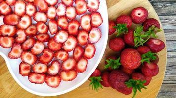 jordgubbar i en vit tallrik med ett hjärta bredvid hela bär foto