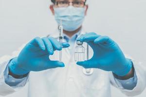 läkare lämnar in blå handskar som håller coronavirus, covid-19-vaccin foto