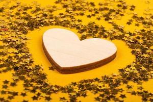 kärlekssymbol trähjärta på gul bakgrund, alla hjärtans dag, mors dag. foto