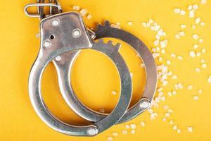 handbojor och kristallmedicin på gul bakgrund, gripande av en droghandlare. foto