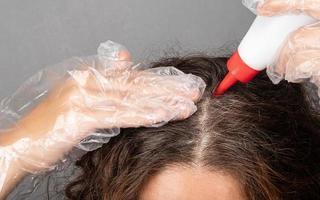 en kvinna applicerar färgämne på hårets rötter målar grågrått hår. foto