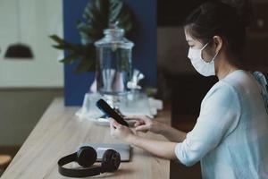 ung asiatisk kvinna som bär mask i café foto