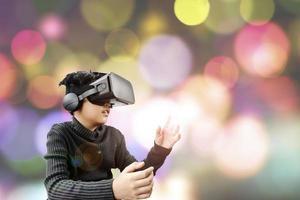 asiatisk tonåring bär vr -glasögon headset med färgglad bakgrund foto