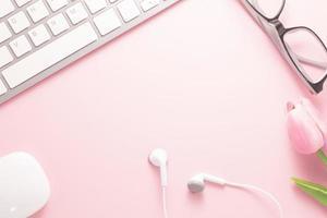 kontorsdiskbord ovanifrån med kontorsmaterial, rosa bord med kopieringsutrymme, arbetsplatskomposition i rosa färg, platt läggning foto