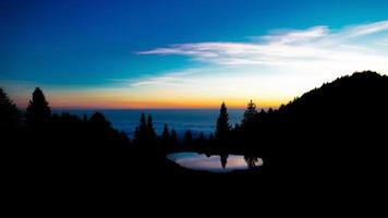 efter solnedgången färgerna i ett alpint landskap med en liten sjö foto
