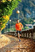 idrottsman man springer på hösten bland bladen foto