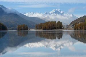 höstlandskap av en sjö i de schweiziska alperna i engadine val foto