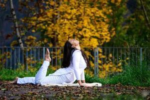 flicka i vitt i yogaställning i parken foto