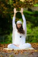 i höstparken utövar en ung kvinna ensam yoga foto