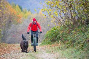 man på en cykel med sin hund på gatan i skogen foto