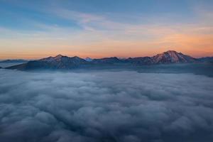 berg spirar från låga moln foto