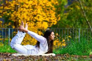 yogaställning av en ung kvinna i parken på hösten foto