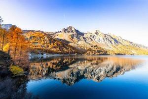 schweiziskt alplandskap med en engadinsjö och speglat berg foto