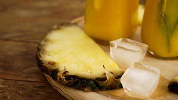 färska ananasskivor och och isbitar på en träbakgrund foto