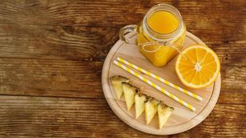 flaskor med ananasjuice på ett träbord. foto