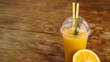 apelsinjuice i snabbmat stängd kopp med rör på träbord foto
