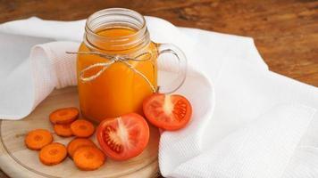 färsk morot och tomatjuice i glas på träbord foto