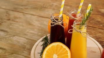 hemgjord limonad i små flaskor. mångfärgade juicer och frukter foto