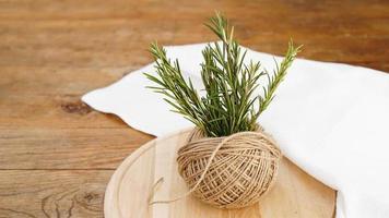 kvistar av rosmarin och nøster av jutrep på ett trä foto